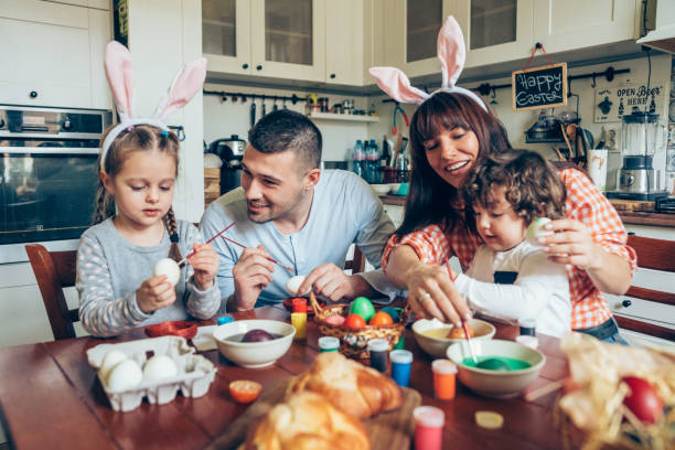 Happy family painting Easter eggs Lovely family prepare for Easter at domestic kitchen religious celebration stock pictures, royalty-free photos & images