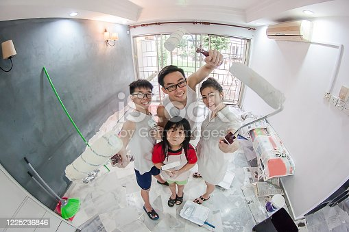 A happy family painting their new house with smiling face on camera