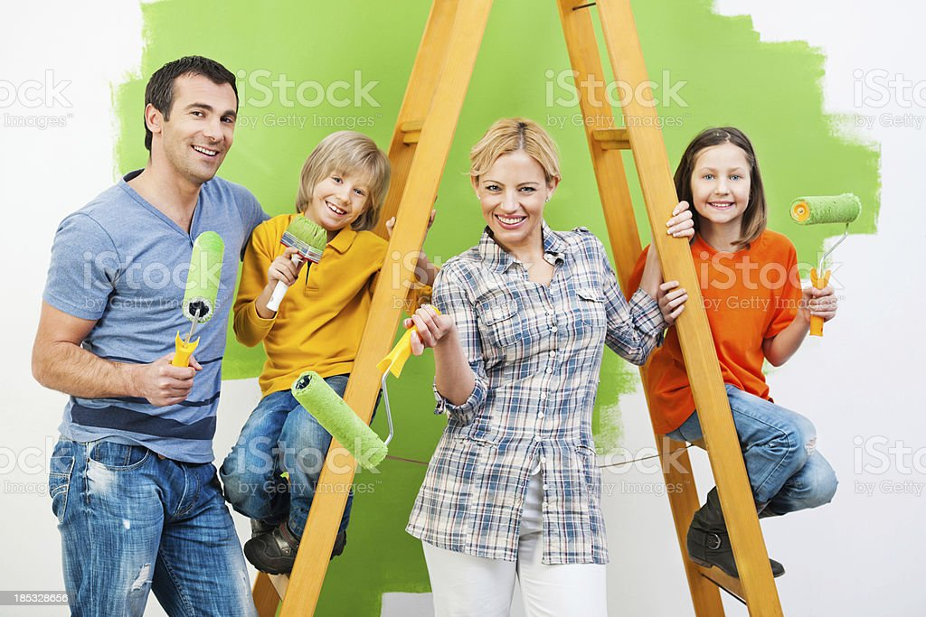 Happy family painting wall in green. royalty-free stock photo
