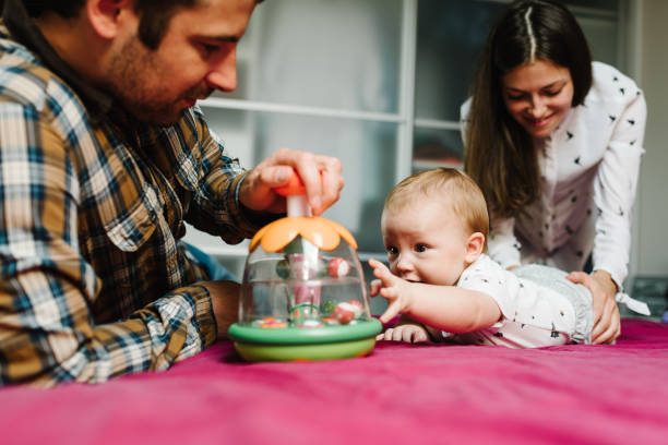 Happy family, parenthood and people concept - mother, father with baby lying in bed at home. Portrait of young smiling family with son playing with toy.