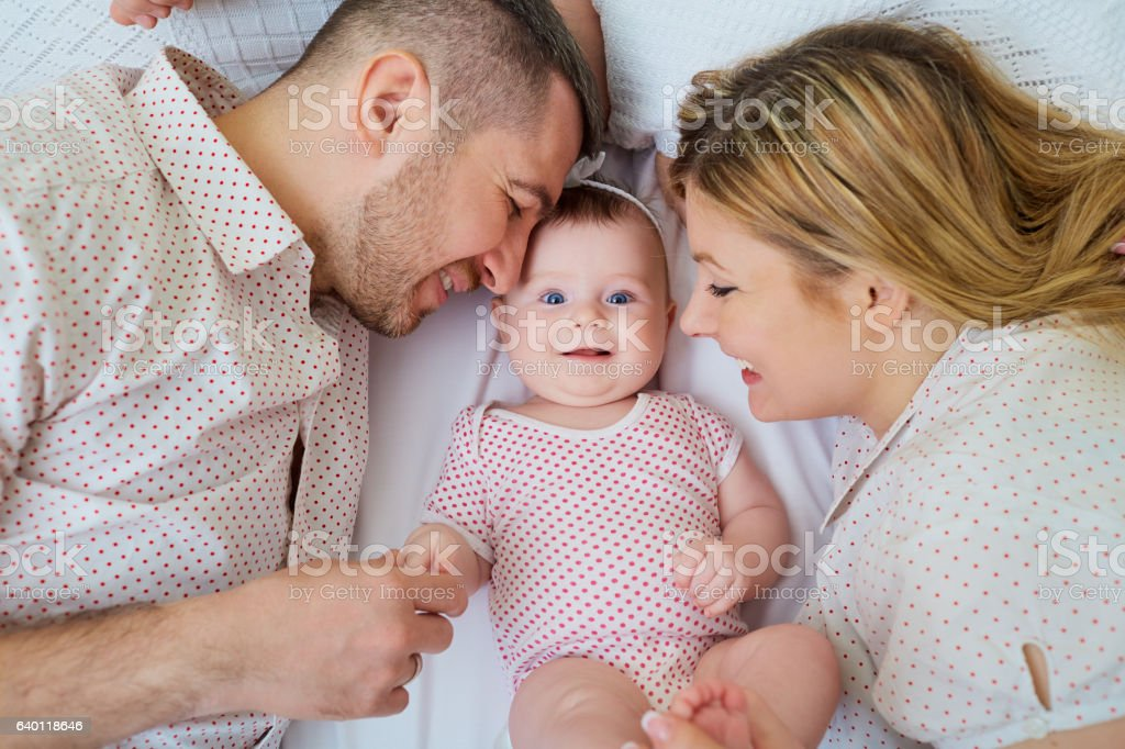 Happy family. Parents with baby on the bed. Closeup – Foto