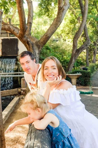 glückliche familie - eltern mit kleinkind mädchen spaß im zoo. familienerholung, verbringen zeit zusammen konzept. vertikale karte. selektiven fokus. kopieren sie raum. - vorschulzoothema stock-fotos und bilder
