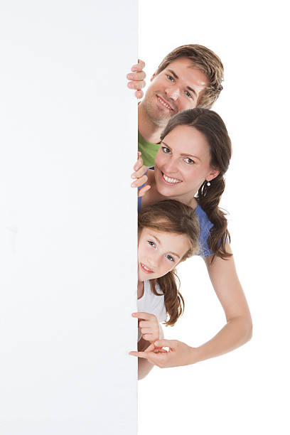 happy family peeking from blank billboard - mom spying stock photos and pictures