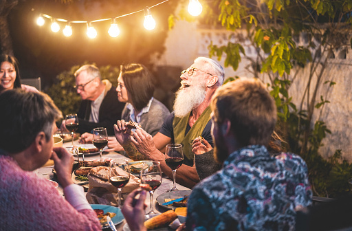 Happy family people having fun at barbecue dinner - Multiracial friends eating at bbq meal - Food, friendship, gathering and summer lifestyle concept - Focus on hipster man left hand