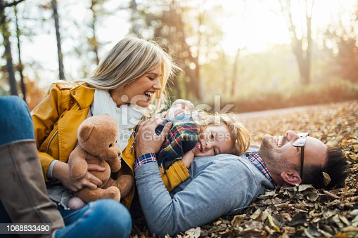 Happy family smiling and lying on ground with autumn leaves.