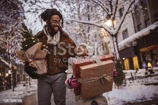 Young family preparing for Christmas holiday. They walking on street and  holding gift boxes and Christmas tree