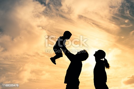 Silhouette of happy mother and father having fun playing with child at sunset.