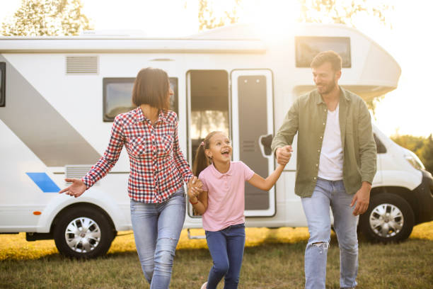 Happy family Family camping in a recreational vehicle. About 30 years old parents and a 8 years old daughter, all Caucasian people. motor home stock pictures, royalty-free photos & images