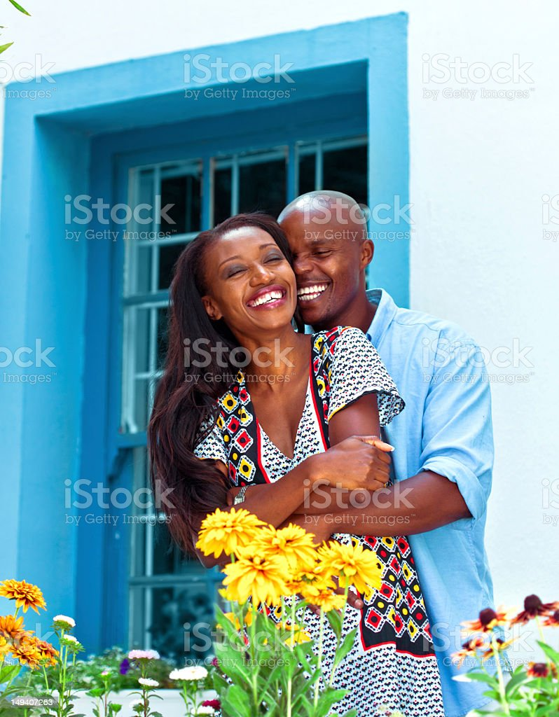 Happy family Happy african couple embracing in front of their house. Adult Stock Photo