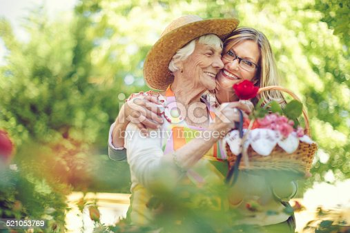 Senior woman and her adult daughter gardening on a nice summer day