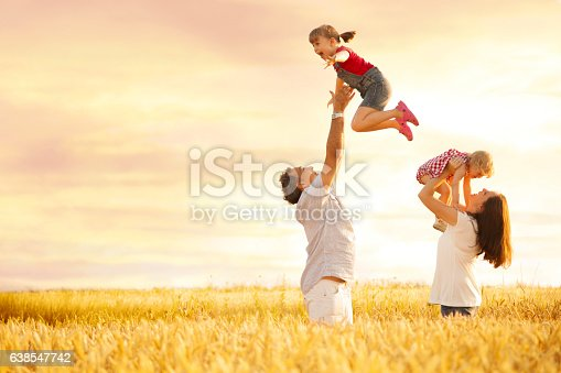 Young playful father is playing with daughter in the field  by throwing up a happy girl in the air and catching her while mother is holding a baby girl.