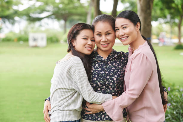 Happy family Happy Vietnamese daughter, mother and grandmother hugging and looking at camera vietnamese ethnicity stock pictures, royalty-free photos & images