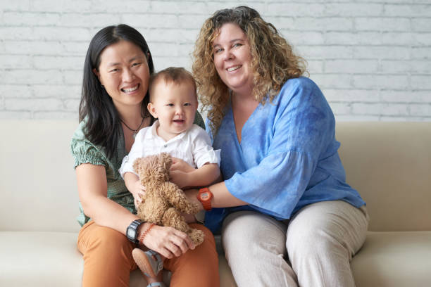 Happy family Happy multi-ethnic female couple with their adorable baby boy gay person stock pictures, royalty-free photos & images
