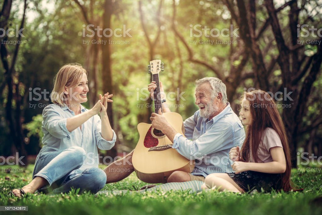 Happy family play guitar and sing together in park стоковое фото