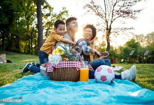 Happy family play guitar and sing together while sitting in the park in summer.