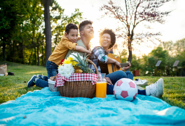 happy family play guitar and sing together while sitting in the park in summer. - picnic foto e immagini stock