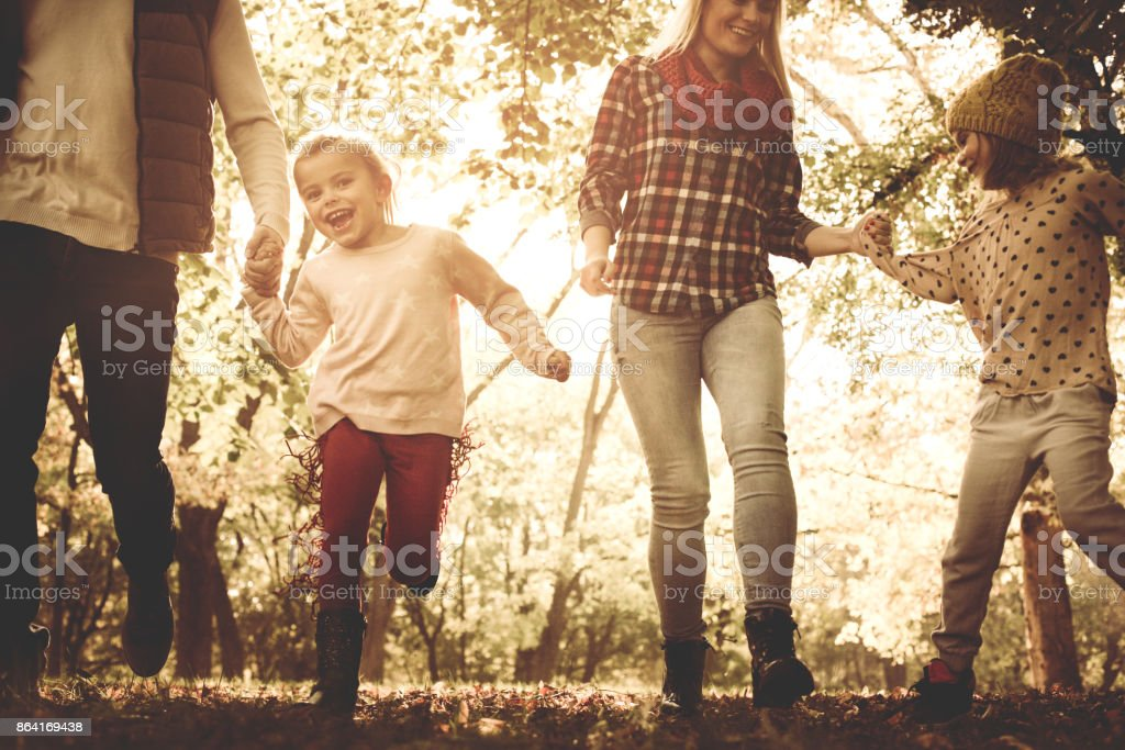 Happy family playing and running trough park together. royalty-free stock photo