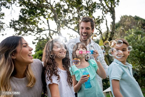 Portrait of a happy Latin American family having fun playing at the park making bubbles and laughing - summer lifestyle concepts