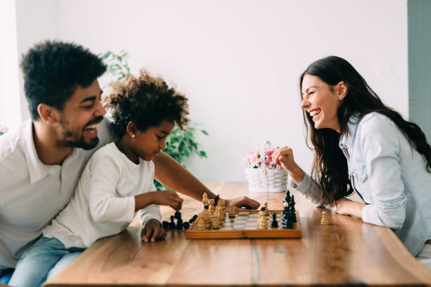 Happy family playing chess together at home stock photo