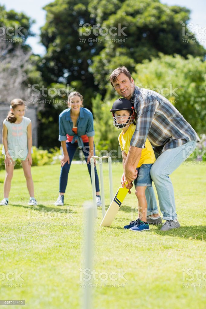 Happy family playing cricket together royalty-free stock photo