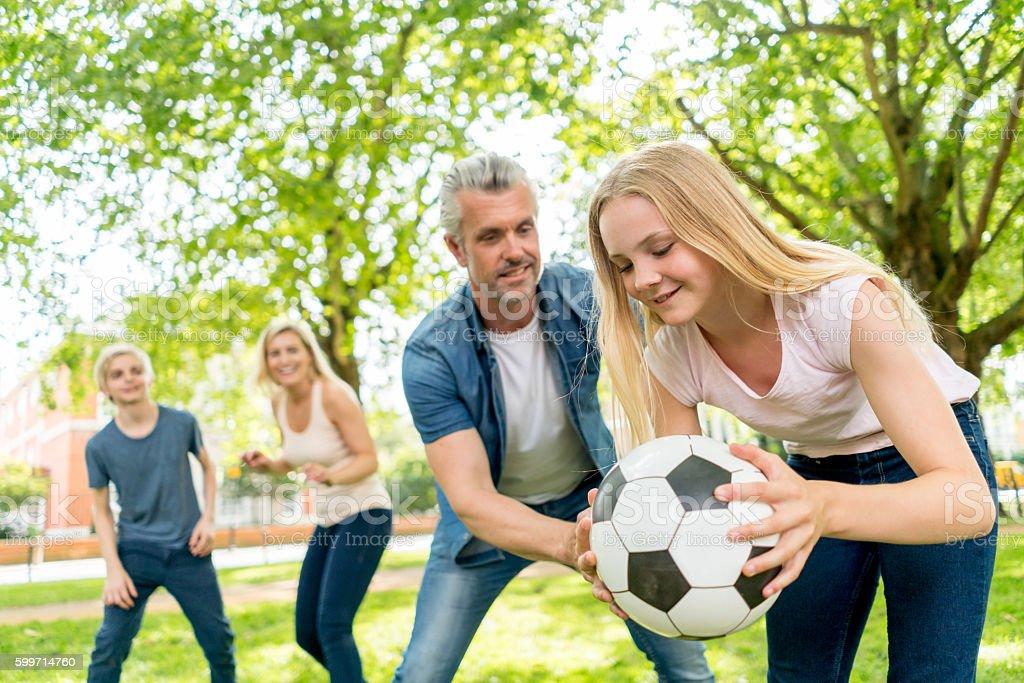 Happy family playing football stock photo