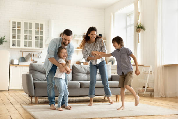 Happy family playing funny game having fun together. stock photo