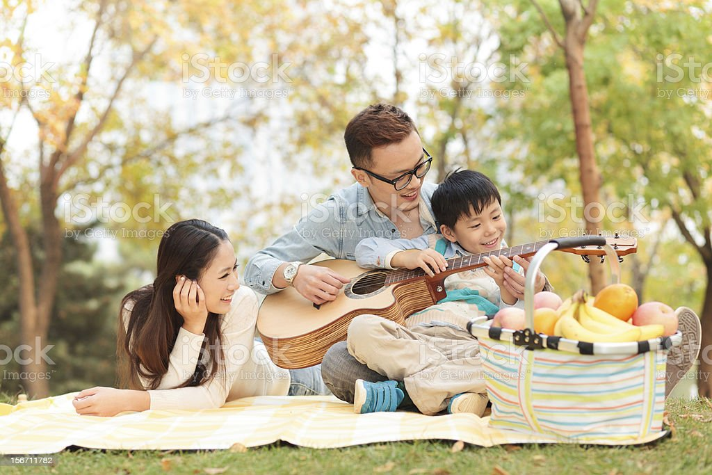 happy family playing guitar in park stock photo