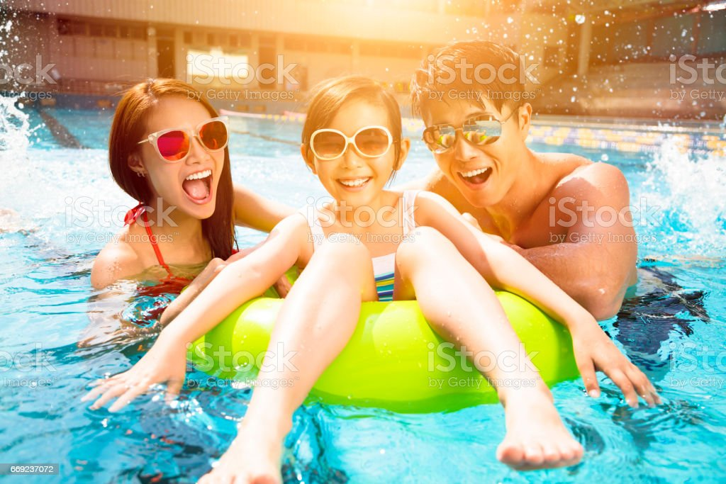 Happy family playing in swimming pool stock photo