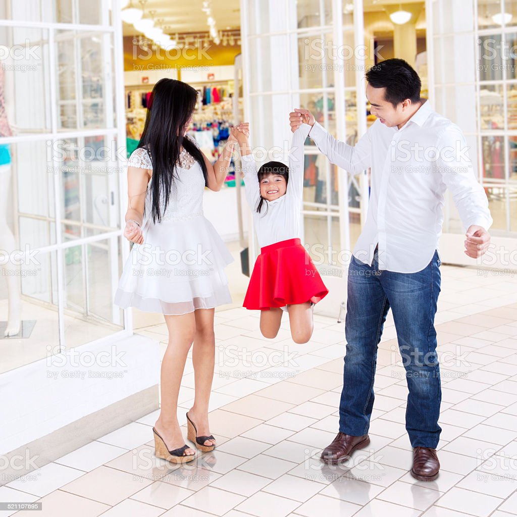 Happy family playing in the mall stock photo