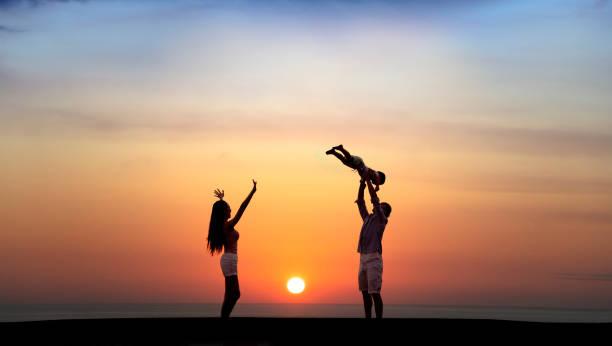 夕暮れ時にビーチで遊ぶ幸せな家族 - シンプルな暮らし ストックフォトと画像