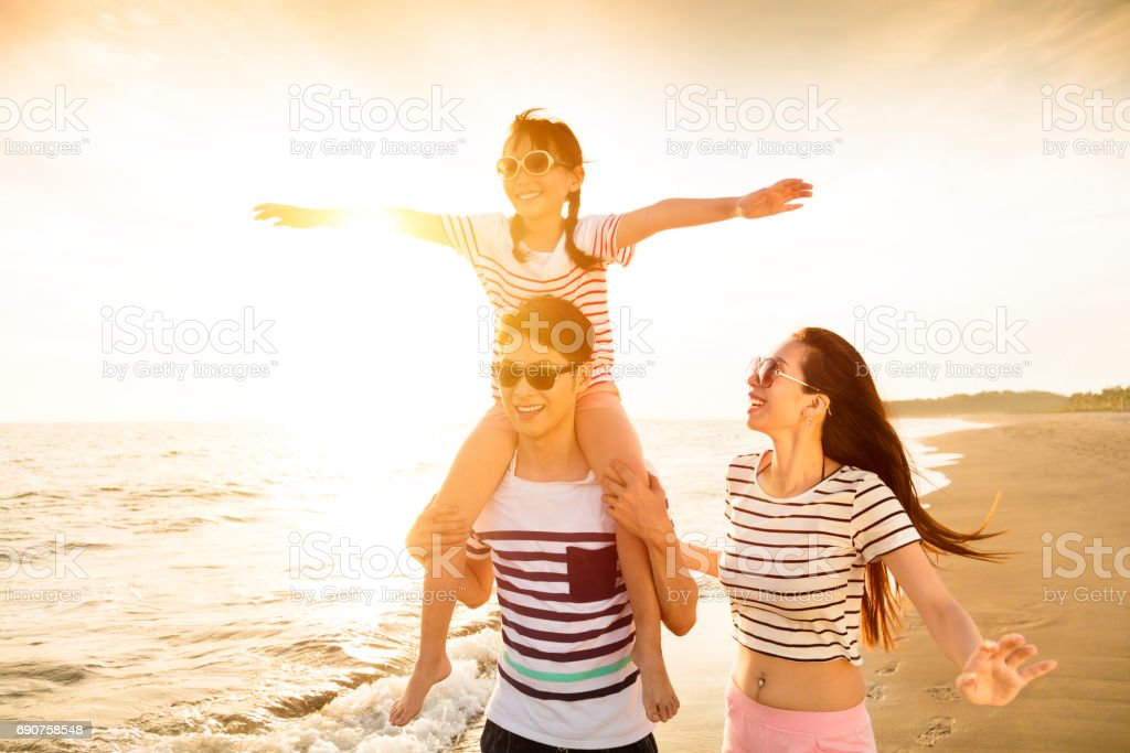 happy family playing on the beach at sunset stock photo