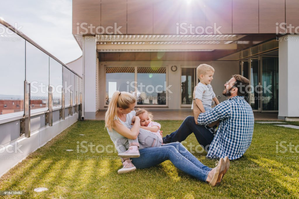 Happy family playing on the grass in front of their penthouse. stock photo