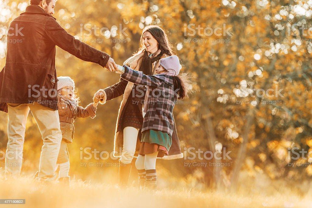 Famille heureuse, jouant anneau autour de la rose à l'automne. - Photo