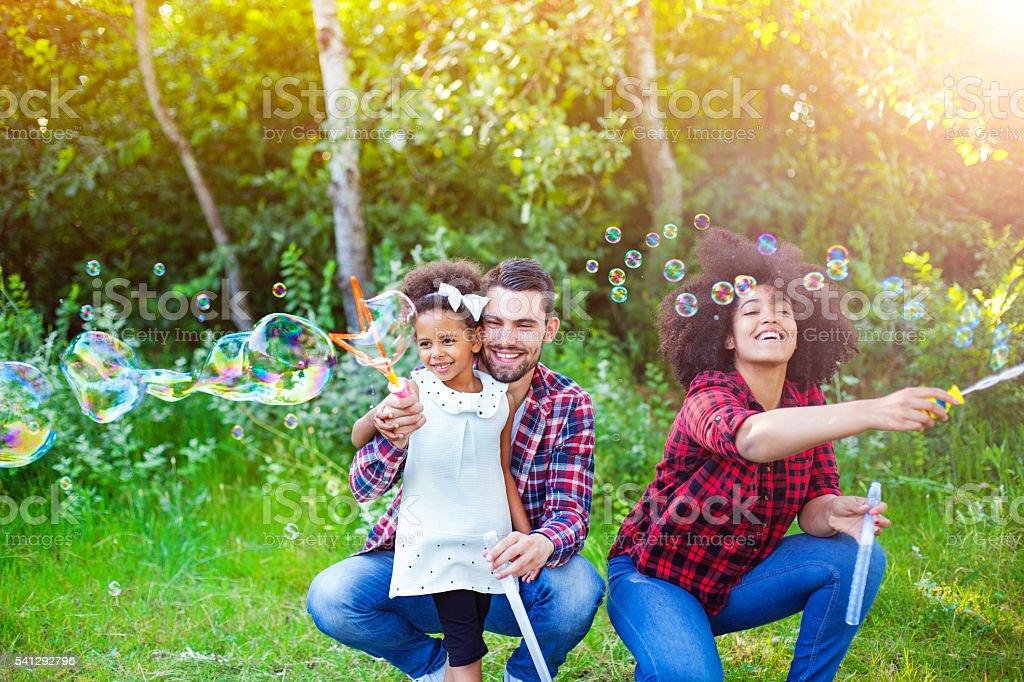 Família feliz brincando com bolhas de sabão no parque. - foto de acervo
