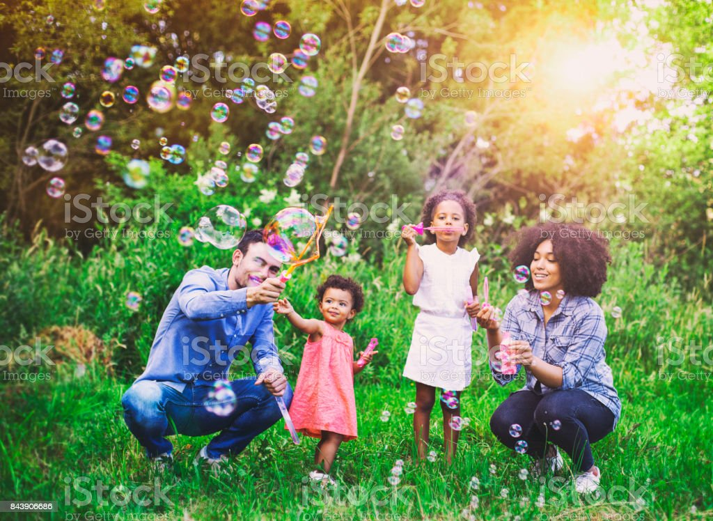 Happy family playing soap bubbles in park. stock photo