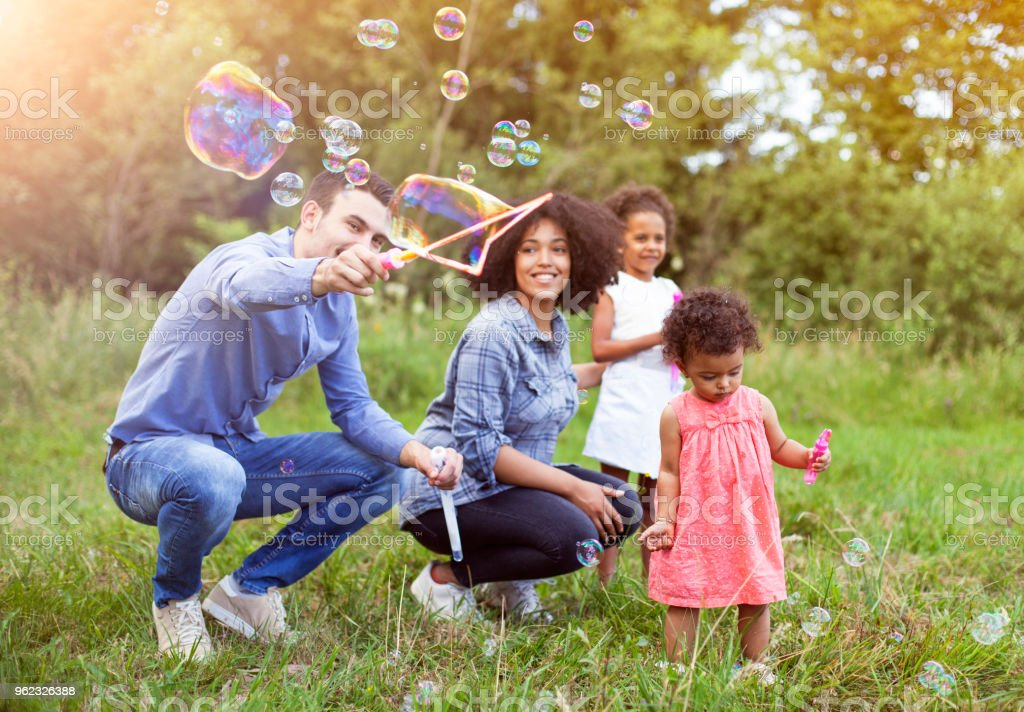 Happy Family Playing Soap Bubbles In Park Stock Photo