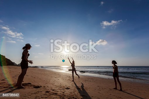 A DSLR Canon photo of a mother and her young daughters playing volleyball at Praia do Boldró, Fernando de Noronha, Pernambuco, Brazil. They are silhouetted against the setting sun low on the horizon.