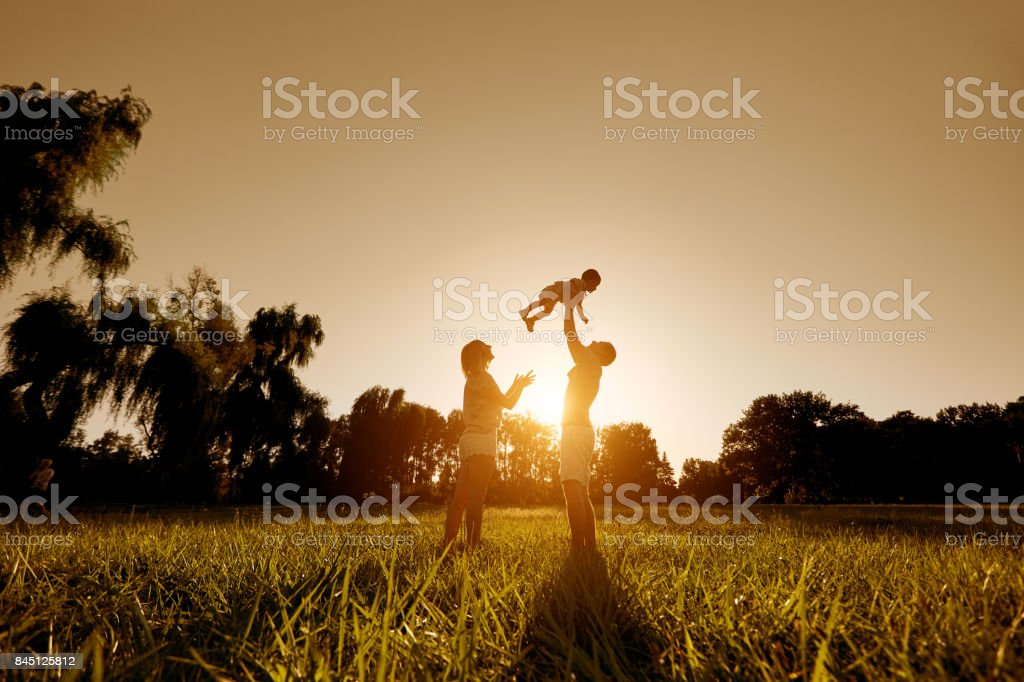 Happy family playing with a child at sunset in the park. stock photo