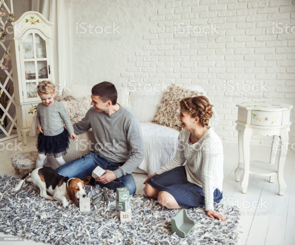 Happy Family Playing With A Pet Dog In The Spacious Living Room ...