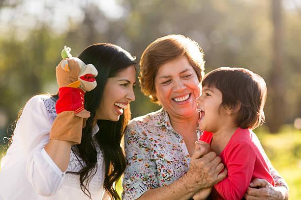 glückliche familie spielen mit einer puppe - kinder picknick spiele stock-fotos und bilder