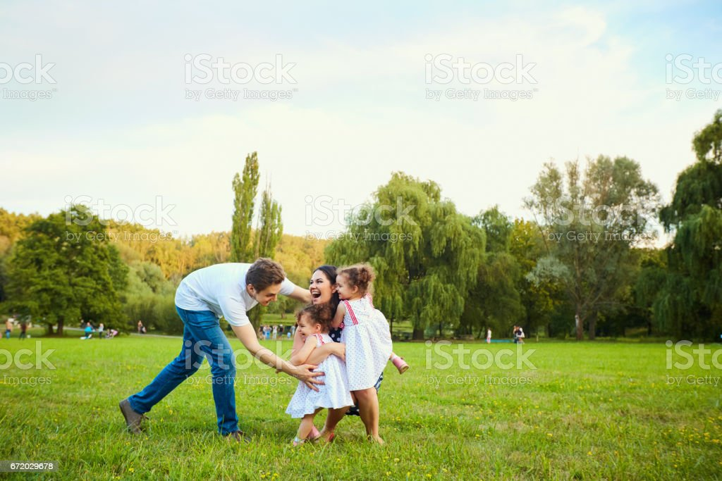 Happy family playing with children in the park stock photo