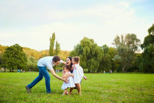 glückliche familie mit kindern im park spielen - kinder picknick spiele stock-fotos und bilder