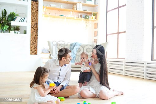 954356678 istock photo Happy family playing with colorful blocks at home 1206643862