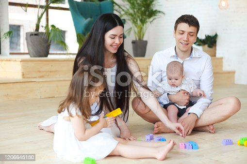 954356678 istock photo Happy family playing with colorful blocks at home 1206645150