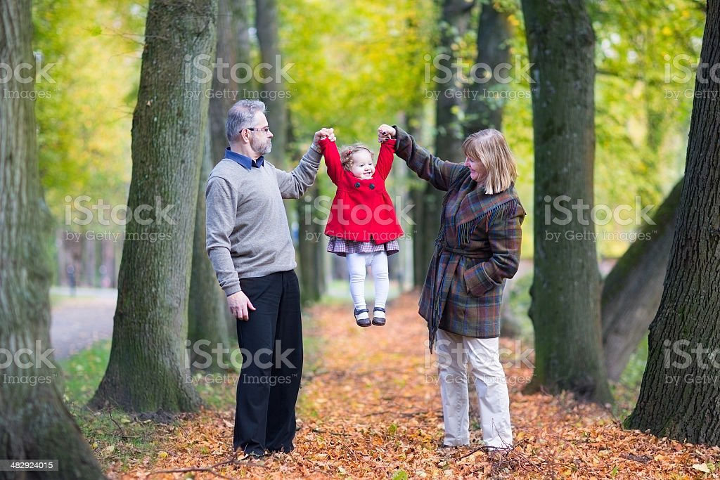 Happy family playing with little toddler girl in autumn park stock photo