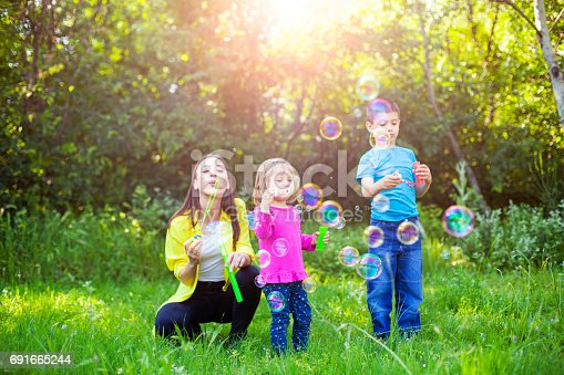 Happy Family Playing With Soap Bubbles Stock Photo & More