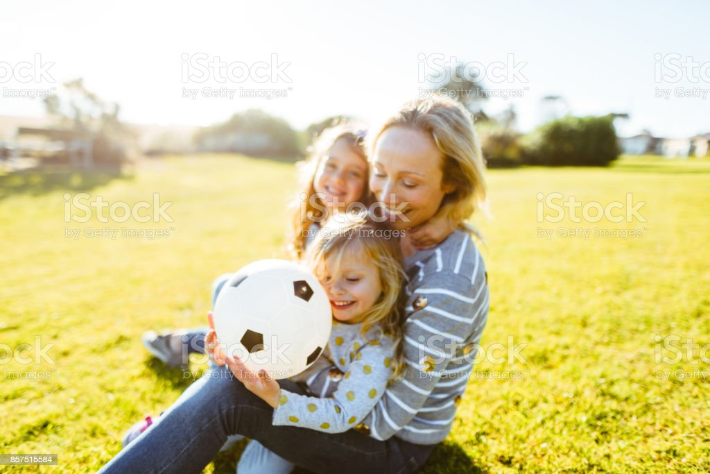 happy family playing with soccer ball at park stock photo