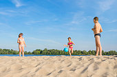 Happy family plays beach volleyball. Healthy lifestyle.