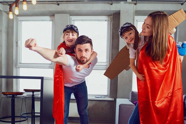 Eine glückliche Familie spielt in Superhelden im Innenbereich – Foto