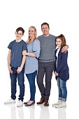 Studio shot of parents with their children standing and posing for camera on white background - Family portrait